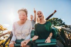 Giovani amici entusiasti che guidano giro del parco di divertimenti Fotografia Stock