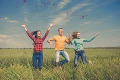 Giovani amici felici che corrono sul giacimento di grano verde Immagini Stock