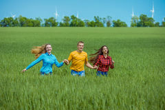 Giovani amici felici che corrono sul giacimento di grano verde Fotografie Stock Libere da Diritti