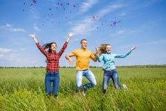 Giovani amici felici che corrono sul giacimento di grano verde Fotografia Stock Libera da Diritti