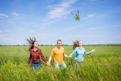 Giovani amici felici che corrono sul giacimento di grano verde Fotografie Stock