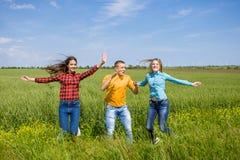 Giovani amici felici che corrono sul giacimento di grano verde Immagine Stock