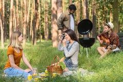 Giovani amici felici che fanno picnic in foresta Fotografia Stock Libera da Diritti