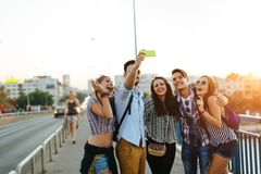 Giovani amici felici che prendono selfie sulla via Immagini Stock Libere da Diritti