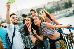 Giovani amici felici che prendono selfie sulla via Fotografia Stock