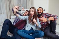 Giovani amici felici che si siedono e che prendono selfie a casa Immagini Stock
