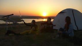 Giovani amici felici che si siedono sull'erba e che si divertono insieme al tramonto all'aperto video d archivio