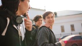 Giovani amici felici in vestiti scuri che camminano sulla via video d archivio