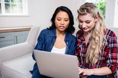 Giovani amici femminili allegri che guardano in computer portatile fotografia stock libera da diritti