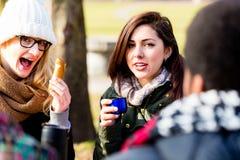 Giovani amici femminili che bevono una bevanda calda all'aperto nell'inverno Fotografia Stock