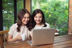 Giovani amici femminili che praticano il surfing insieme Internet su un computer portatile Immagine Stock
