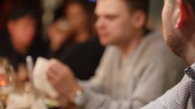 Giovani amici maschii che parlano mentre avendo bevande insieme alla barra di classe interna con illuminazione interna morbida archivi video