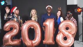 Giovani amici Multi-etnici che ballano alla festa di Natale in studio Movimento lento stock footage