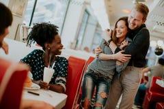 Giovani amici multirazziali che godono nella cena fotografie stock