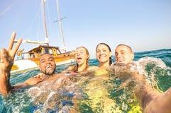 Giovani amici multirazziali che prendono selfie e che nuotano durante il giro della barca a vela Fotografia Stock