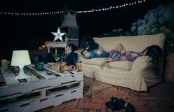Giovani amici potabili che dormono in un sofà dopo il partito immagini stock libere da diritti