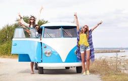 Giovani amici sorridenti di hippy sopra l'automobile del furgoncino fotografie stock libere da diritti