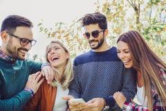 Giovani amici sorridenti felici che camminano all'aperto nel parco Fotografia Stock Libera da Diritti