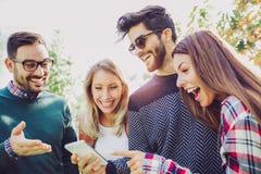 Giovani amici sorridenti felici che camminano all'aperto nel parco Fotografie Stock