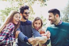 Giovani amici sorridenti felici che camminano all'aperto nel parco Immagini Stock Libere da Diritti