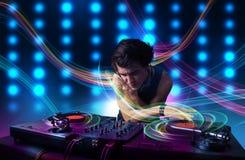 Giovani annotazioni di miscelazione del DJ con le luci variopinte Fotografie Stock Libere da Diritti