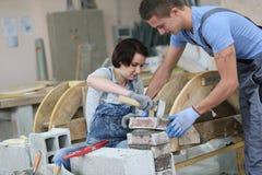 Giovani apprendisti nell'addestramento della muratura Fotografia Stock Libera da Diritti