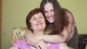 Giovani approcci della figlia e delicatamente abbracciare madre anziana stock footage