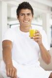 giovani arancioni beventi dell'uomo della spremuta Immagine Stock