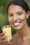 giovani arancioni beventi della donna della spremuta immagine stock libera da diritti