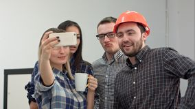 Giovani architetti felici che prendono i selfies divertenti in ufficio immagine stock