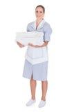 Giovani asciugamani felici della tenuta della domestica immagini stock