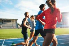 Giovani atleti che corrono sulla pista di corsa in stadio immagine stock libera da diritti