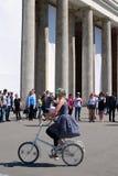 Giovani attori che eseguono nel parco di Gorkij Una donna guida una bicicletta Fotografie Stock