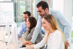 Giovani attraenti che prendono un corso di formazione con il formator Immagine Stock