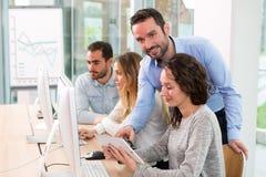 Giovani attraenti che prendono un corso di formazione con il formator Immagini Stock
