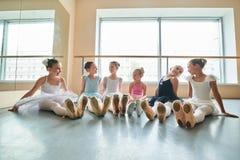 Giovani ballerine felici che si siedono sul pavimento Fotografia Stock