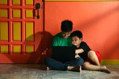 Giovani bambini asiatici, fratelli o fratelli germani, con un computer portatile in un salone Fotografia Stock Libera da Diritti