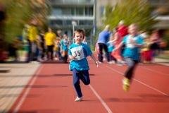 Giovani bambini in età prescolare, correre sulla pista in un competi maratona immagine stock libera da diritti