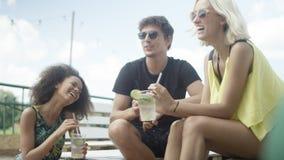 Giovani bei amici della corsa mista che si siedono sui lettini sotto l'ombrello e che godono della vacanza immagini stock
