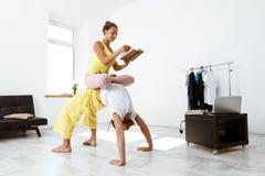 Giovani bei asanas allegri di yoga del partner di addestramento delle coppie a casa Fotografia Stock