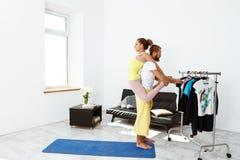Giovani bei asanas allegri di yoga del partner di addestramento delle coppie a casa Immagine Stock Libera da Diritti