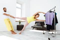 Giovani bei asanas allegri di yoga del partner di addestramento delle coppie a casa Fotografia Stock Libera da Diritti