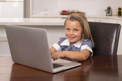 Giovani bei ed anni dolci delle bambine 6 - 8 con capelli biondi e gli occhi azzurri che si siedono a casa cucina che gode con il Immagini Stock