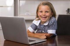 Giovani bei ed anni dolci delle bambine 6 - 8 con capelli biondi e gli occhi azzurri che si siedono a casa cucina che gode con il Immagine Stock Libera da Diritti
