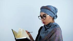 Giovani bei occhiali d'uso arabi della donna di affari che girano la penna di tenuta delle pagine del taccuino su fondo bianco is stock footage