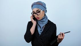 Giovani bei occhiali d'uso arabi della donna di affari che giudicano pianificatore e penna che hanno conversazione con il partner stock footage