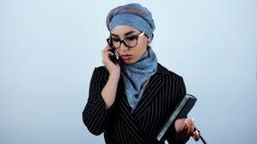 Giovani bei occhiali d'uso arabi della donna di affari che giudicano pianificatore e penna che hanno conversazione sullo smartpho video d archivio