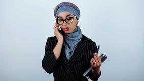 Giovani bei occhiali d'uso arabi della donna di affari che tengono pianificatore che ha conversazione sullo smartphone sull'isola video d archivio
