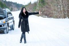 Giovani bei problemi di segnalazione della donna con l'automobile rotta sulla vittoria Immagine Stock