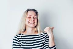 Giovani bei punti biondi sorridenti della donna un dito via isolato su fondo bianco Emozioni positive, espressione facciale, fotografia stock